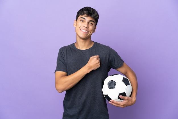 Young football player man on isolated purple celebrating a victory
