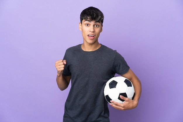 勝者の位置での勝利を祝う孤立した紫色の壁の上の若いサッカー選手の男