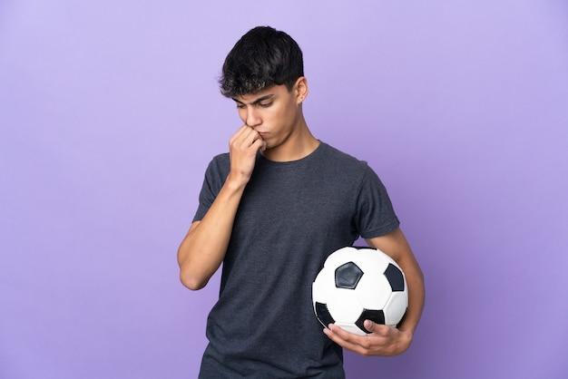 Молодой футболист человек над изолированной фиолетовой стеной с сомнениями