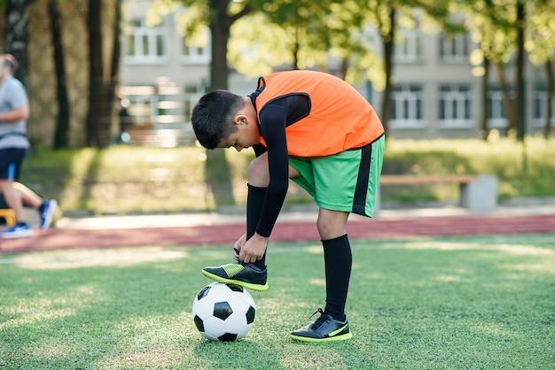 ボールの上に立っている靴ひもを結ぶ若いサッカー選手。
