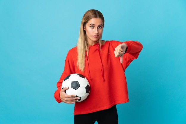 Young football player woman on blue showing thumb down with negative expression