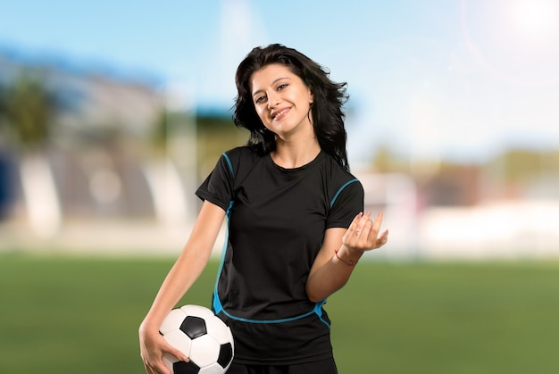 Young football player woman inviting to come with hand. happy that you came at outdoors