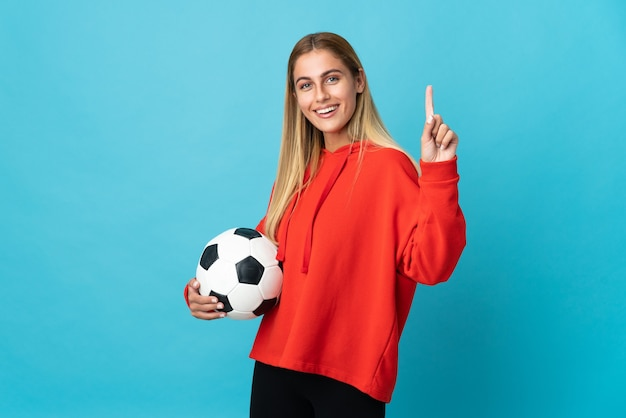Young football player woman isolated on blue background showing and lifting a finger in sign of the best