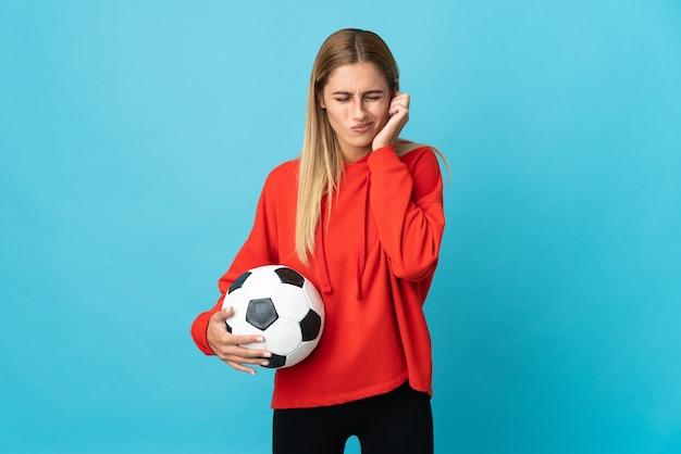 Женщина молодого футболиста изолирована на синем пространстве разочарована и закрывает уши