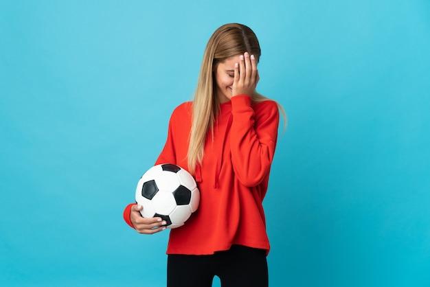 Молодая женщина-футболист изолирована на синей стене с усталым и больным выражением лица
