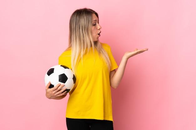 手のひらに架空のコピースペースを保持しているピンクの壁に分離された若いサッカー選手の女性