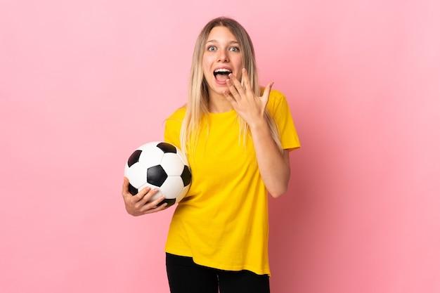 Молодой футболист женщина изолирована на розовом с удивленным выражением лица