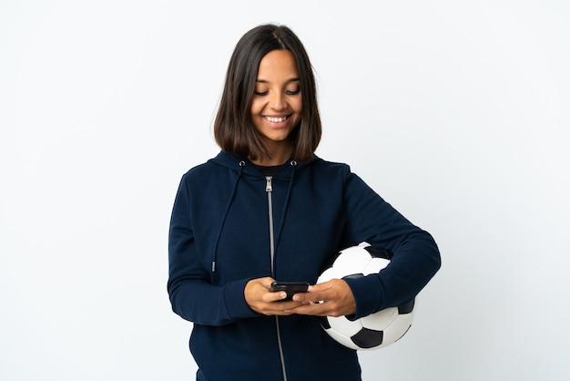 携帯電話でメッセージを送信する白い背景で隔離の若いサッカー選手の女性