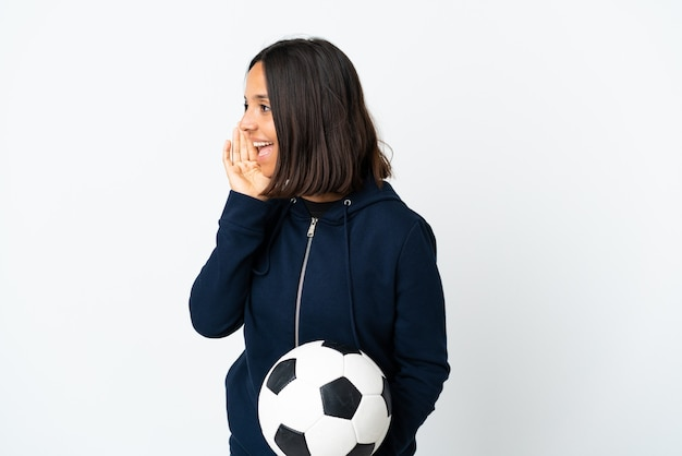 입 벌리고 측면으로 외치는 흰색 배경에 고립 된 젊은 축구 선수 여자