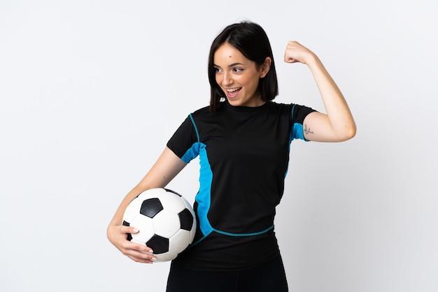 勝利を祝って白い壁に孤立した若いサッカー選手の女性