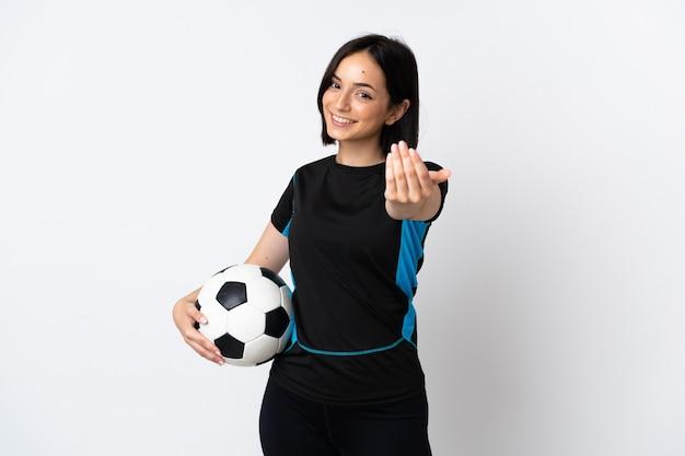 手で来るように誘う白い壁に孤立した若いサッカー選手の女性。あなたが来て幸せ
