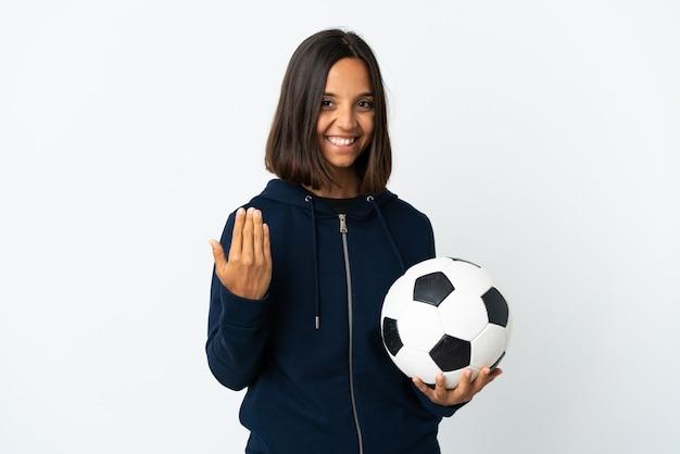 手で来るように誘う白い壁に隔離された若いサッカー選手の女性。あなたが来て幸せ