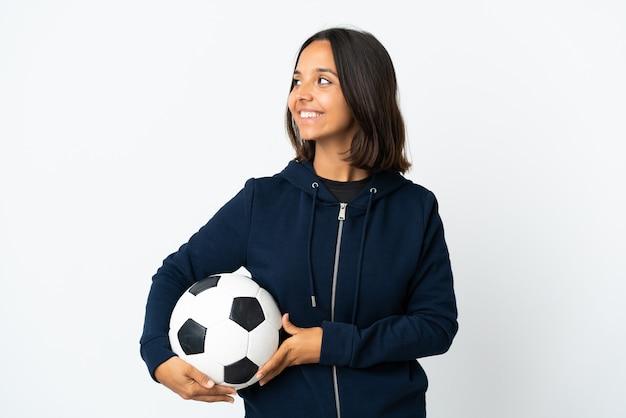 Молодая женщина футболиста изолирована на белой стене смотрящую сторону