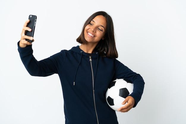 セルフィーを作る白い壁に孤立した若いサッカー選手の女性