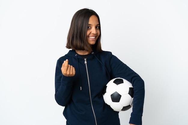 お金のジェスチャーを作る白い壁に分離された若いサッカー選手の女性