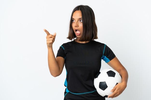 Женщина молодой футболист, изолированные на белой стене, указывая в сторону