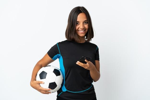 Молодая женщина футболиста изолирована на белой стене, отправляя сообщение с мобильного телефона