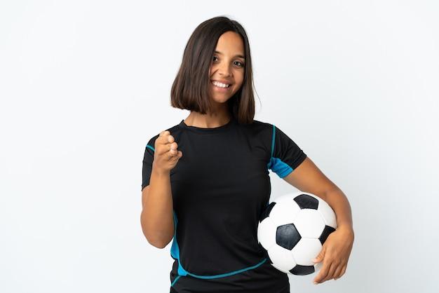 かなりの取引を閉じるために握手する白い壁に孤立した若いサッカー選手の女性