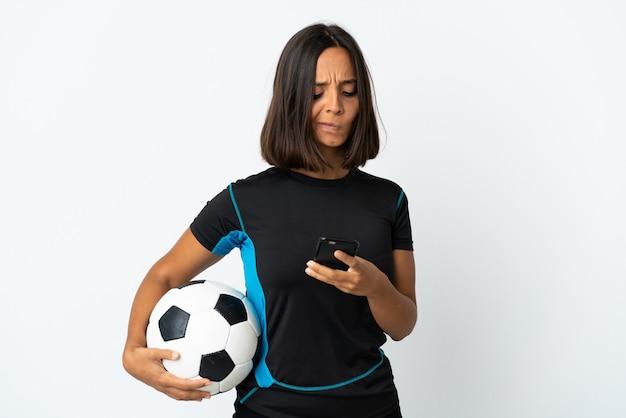 Женщина молодого футболиста изолирована на белой стене, думая и отправляя сообщение