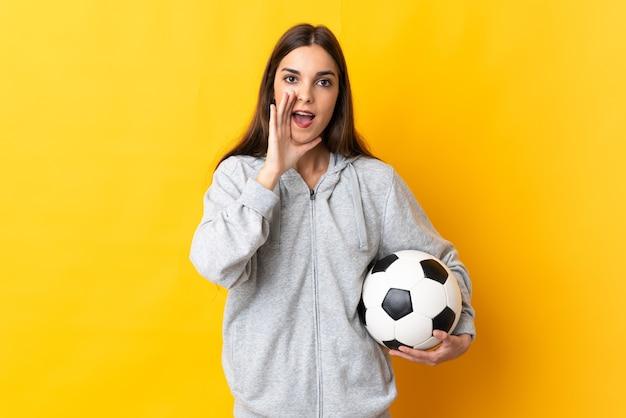 Женщина молодой футболист изолирована на желтом фоне кричит с широко открытым ртом