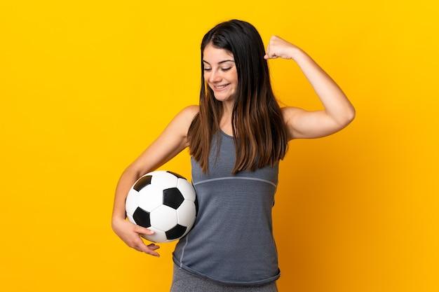 勝利を祝って黄色に孤立した若いサッカー選手の女性
