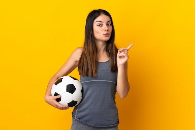 손가락을 들어 올리는 동안 솔루션을 실현하려는 노란색에 고립 된 젊은 축구 선수 여자
