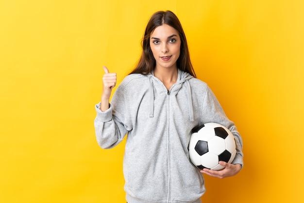Женщина молодого футболиста изолирована на желтой стене, указывая в сторону, чтобы представить продукт