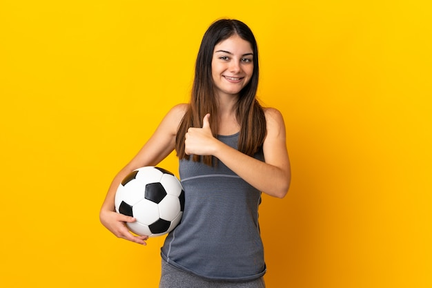 Женщина молодого футболиста изолирована на желтой стене, гордая и самодовольная