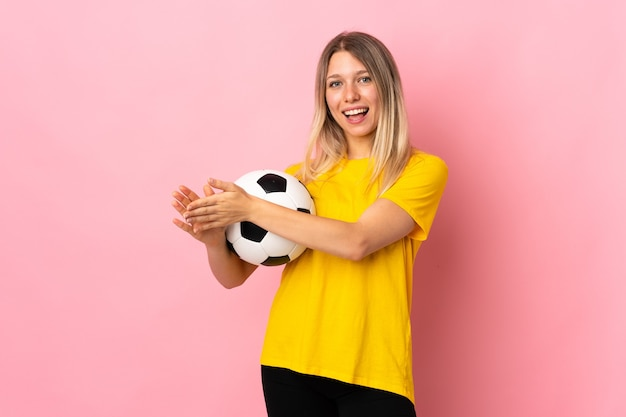 Young football player woman isolated on pink wall applauding