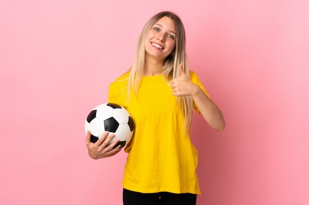 Young football player woman isolated on pink wall giving a thumbs up gesture