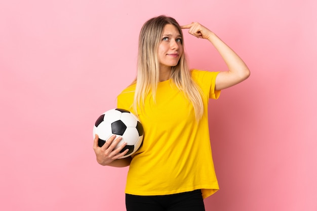 Young football player woman isolated on pink wall having doubts and with confuse face expression