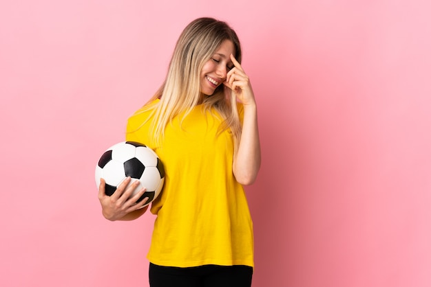 Young football player woman isolated on pink wall laughing