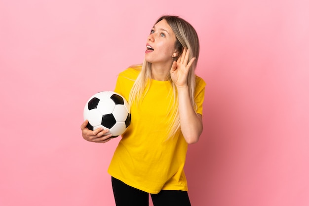 Young football player woman isolated on pink wall listening something