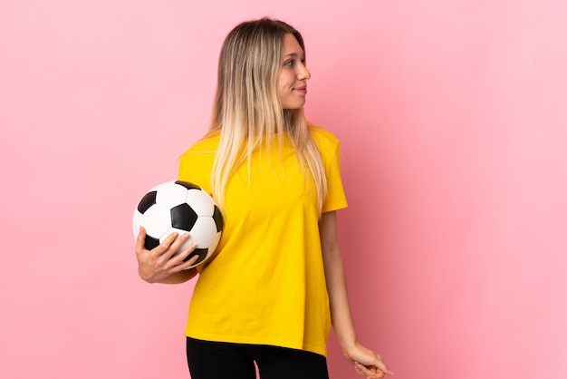 Young football player woman isolated on pink wall looking to the side
