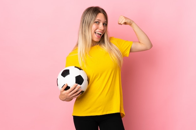 Young football player woman isolated on pink wall making strong gesture