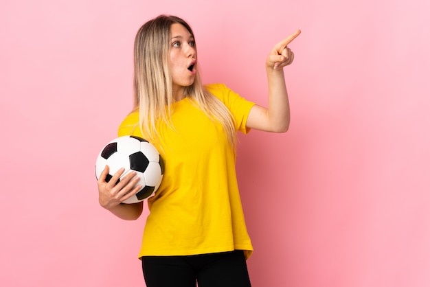 Young football player woman isolated on pink wall pointing away