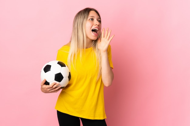 Young football player woman isolated on pink wall shouting with mouth wide open