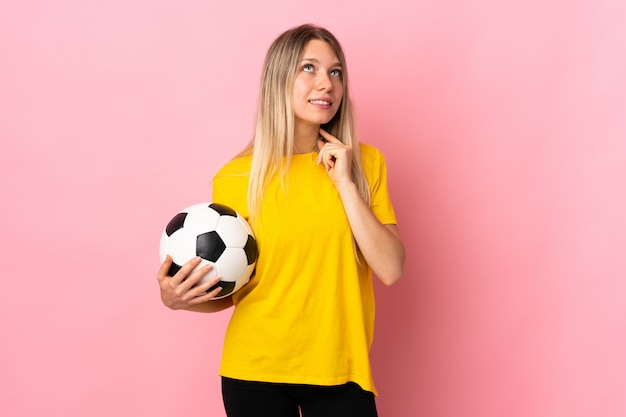 Young football player woman isolated on pink wall thinking an idea