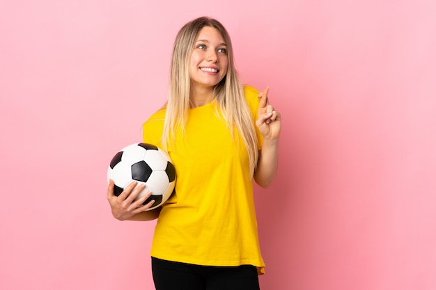 Young football player woman isolated on pink wall with fingers crossing