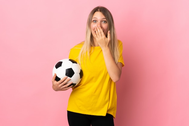 Young football player woman isolated on pink wall with surprise facial expression
