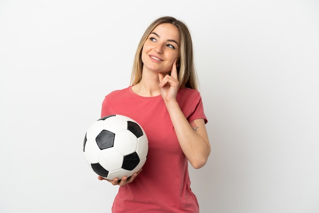 Young football player woman over isolated white wall thinking an idea while looking up