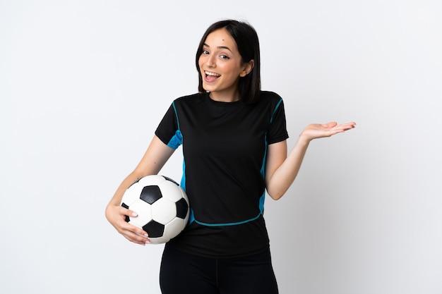 Молодая женщина-футболист изолирована с шокированным выражением лица