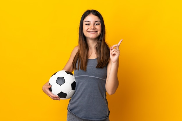 Young football player woman isolated on yellow background showing and lifting a finger in sign of the best