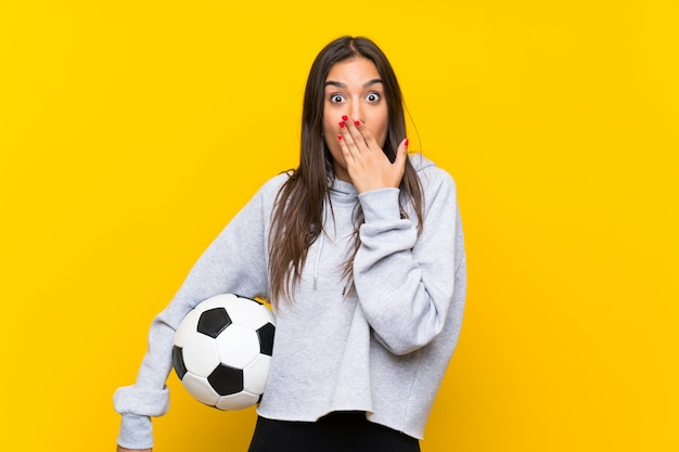 Young football player woman over isolated yellow wall with surprise facial expression
