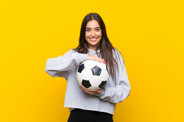 Young football player woman over isolated yellow wall