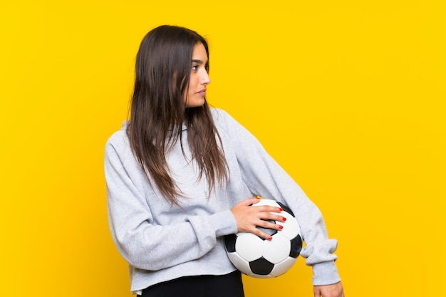 Young football player woman  isolated on yellow