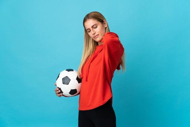 努力したために肩の痛みに苦しんでいる青の若いサッカー選手の女性