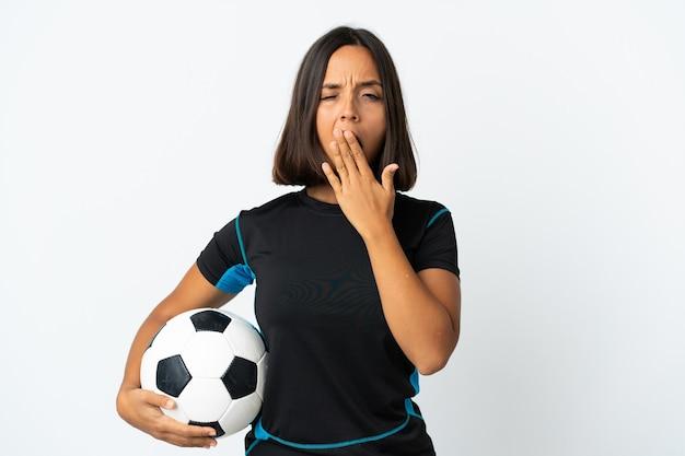 Молодой футболист женщина на белом зевая и прикрывая широко открытый рот рукой