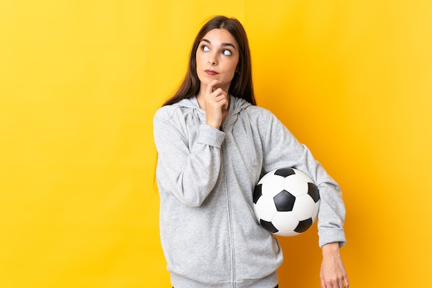 Женщина молодой футболист на желтом, сомневаясь