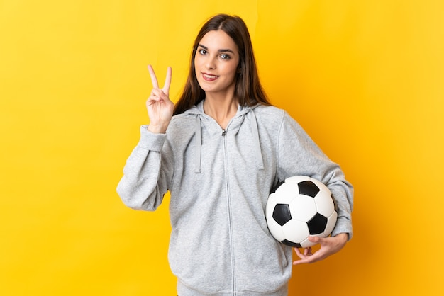 Женщина молодой футболист на желтом улыбается и показывает знак победы